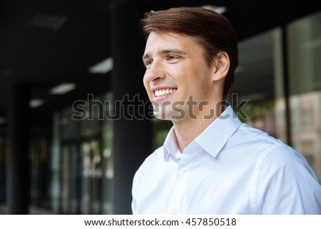 Closeup of smiling handsome young businessman standing near business center - stock photo