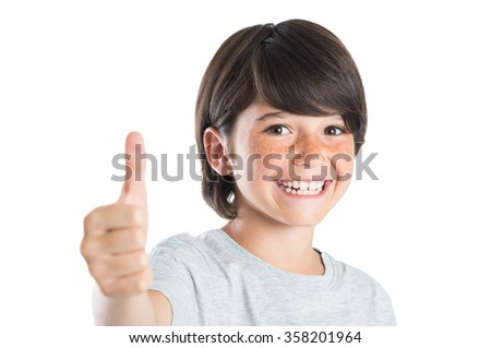 Closeup of smiling little boy showing thumb up gesture isolated on white background. Portrait of happy cute boy showing thumb up and looking at camera. Kid giving you thumbs up. - stock photo