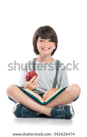 Closeup of smiling little boy studying isolated on white background. Portrait of laughing schoolboy sitting on floor and doing homework. Happy young boy looking at camera with funny face.  - stock photo