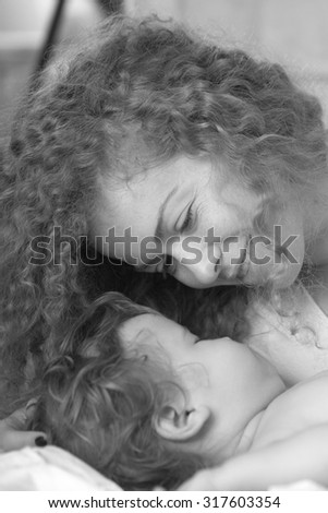 Closeup of smiling tender young loving mother with light blonde curly hair holding little tiny cute male lovely baby indoor in bed with white linen black and white, vertical picture - stock photo