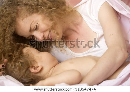 Closeup of smiling tender young loving mother with light blonde curly hair lying with little tiny cute male lovely baby indoor in bed with white linen lying close to each other, horizontal picture - stock photo