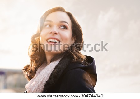 Closeup of smiling thinking woman looking away outdoor - stock photo