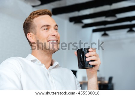 Closeup of smiling young businessman sitting and drinking coffee in office