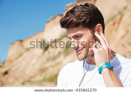 Closeup of smiling young man in earphones listening to music on the beach - stock photo