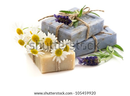 closeup of soap bars with fresh lavender and chamomile flowers isolated on white background