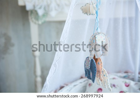 Closeup of soft toys hanging on a cot. - stock photo