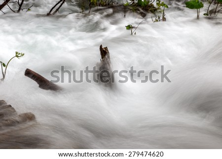 Closeup of Soft water cascading over mountain rocks.Soft Cascading water over mossy rocks - stock photo