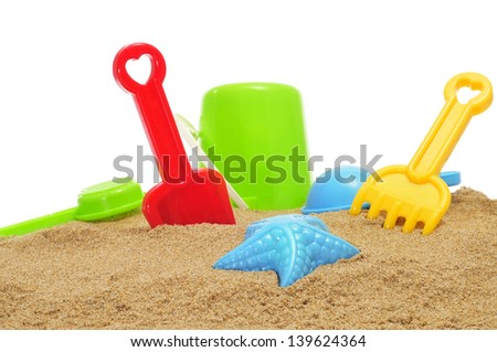 closeup of some beach toys, as a starfish-shaped sand mold, and shovels and rakes of different colors, on the sand of a beach or of a sandpit - stock photo