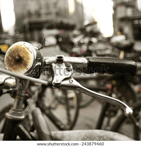 closeup of some bicycles locked in a pole in a street of a city, with a filter effect - stock photo