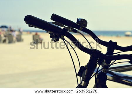 closeup of some bicycles parked in the seafront with blurred people sitting in street benches in the background, with a filter effect - stock photo