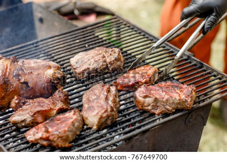 Closeup of some meat skewers being grilled in a barbecue