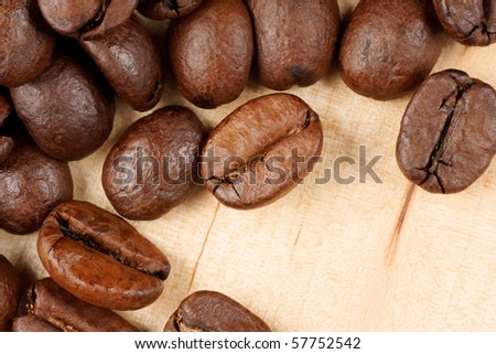 Closeup of some roasted coffee beans over a wooden background with copy space.