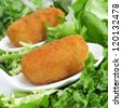closeup of some spanish croquettes in a bed of lettuce served as tapas - stock photo