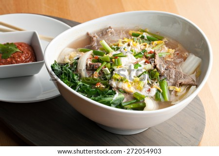 Closeup of some Thai pho style soup with beef and clear rice noodles.