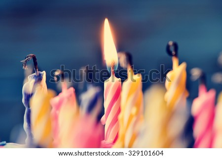 closeup of some unlit candles and just a lit candle after blowing out the cake - stock photo