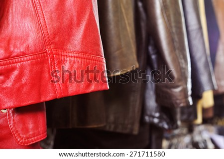 closeup of some used leather clothes, such as jackets and skirts, of different colors hanging on a rack in a flea market - stock photo
