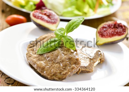 closeup of some veggie cordon bleu in a plate and a plate with salad in the background - stock photo