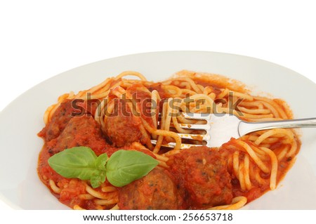 Closeup of spaghetti and meatballs with a fork and sprig of basil - stock photo