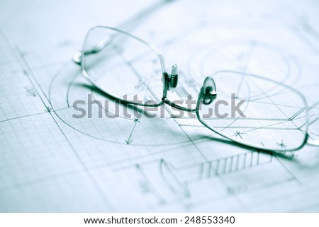 Closeup of spectacles on graph paper with industrial design - stock photo