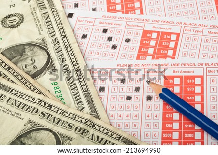 Closeup of sports betting slip with US money  - stock photo