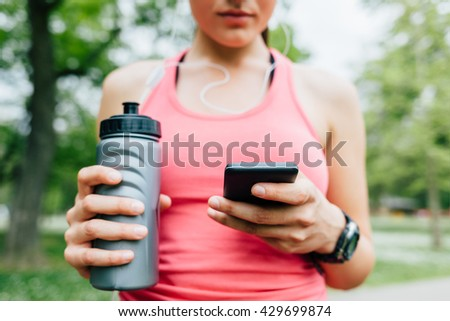Closeup of sporty woman using smart phone after running - stock photo