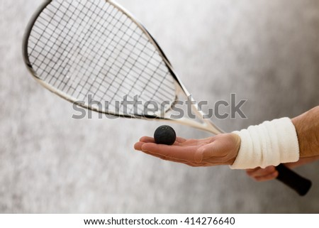Closeup of squash racket and one ball in man's hand. Black-coloured ball represented on man's hand who is on court. - stock photo