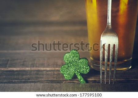 Closeup of St. Patricks Day green shamrock with fork and frosty cold glass of beer on wood board background with room or space for copy, text, words.  Vintage camera instagram treatment for mood - stock photo