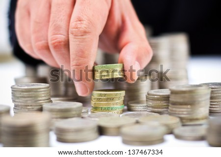 Closeup of stack of british pound coins with a male hand - stock photo
