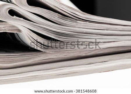 Closeup of stack of newspapers. Assortment of folded newspapers isolated on white. Breaking news, journalism, power of the media, newspaper and magazine ads and subscription concept. - stock photo