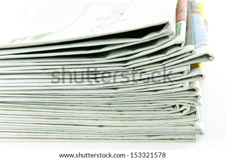 Closeup of stack of newspapers on white