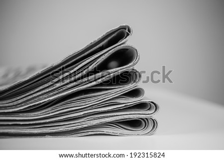 Closeup of stack of newspapers, processed in black and white