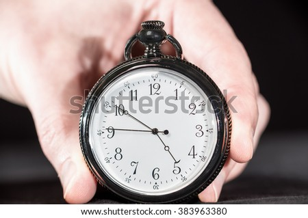 Closeup of steel pocket watch in hand over black background.