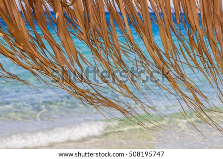 Closeup of straw sunshades detail , turquoise sea in background.
