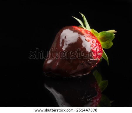 closeup of strawberry in hot chocolate on black background - stock photo