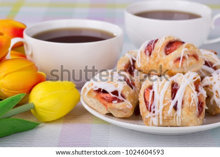 Closeup of strawberry pastries on a plate and coffee with colorful tulips