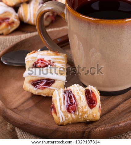 Closeup of strawberry pastries on a wooden plate with a cup of coffee