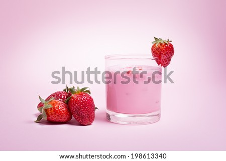 Closeup of strawberry smoothie in a glass and fresh strawberries on pink background.  - stock photo