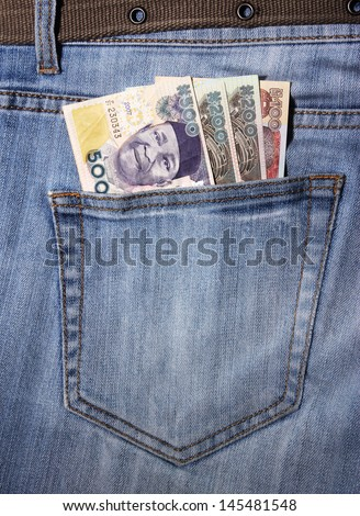 closeup of striped male jeans with nairas in a pocket - stock photo