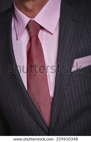 Closeup of stylish office suit with dark grey jacket with handkerchief in the pocket, pink shirt and red necktie.