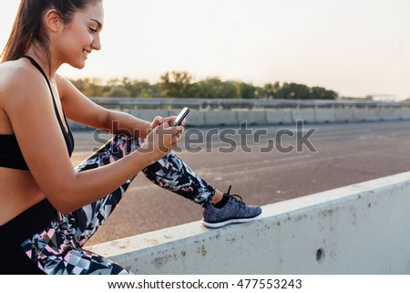 Closeup of stylish sportswoman using mobile phone after workout on the street