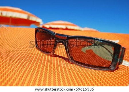 Closeup of sunglasses on orange background and beach with umbrellas in background, Rimini, Italy - stock photo