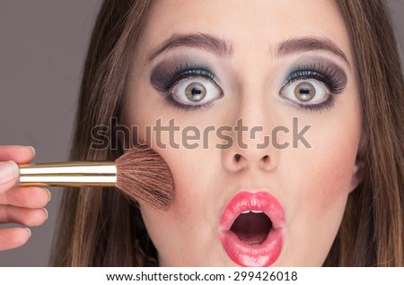 closeup of surprised blond young woman opening eyes while getting cheek makeup done - stock photo