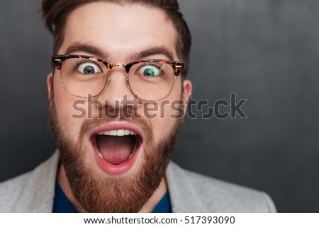 Closeup of surprised happy young businessman in glasses with opened mouth