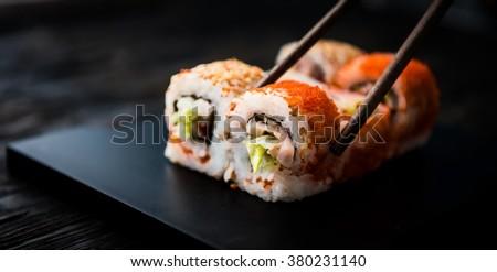 closeup of sushi rolls with chopsticks - stock photo
