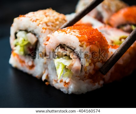 closeup of sushi rolls with chopsticks - stock photo