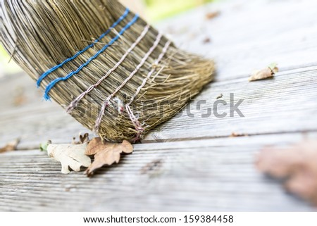 Closeup Of Sweeping Autumn Leaves Off Wooden Patio With A