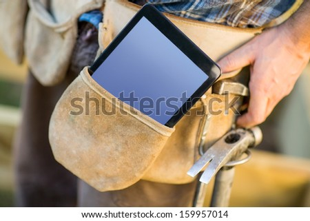 Closeup of tablet computer and hammer in carpenter's tool belt outdoors - stock photo