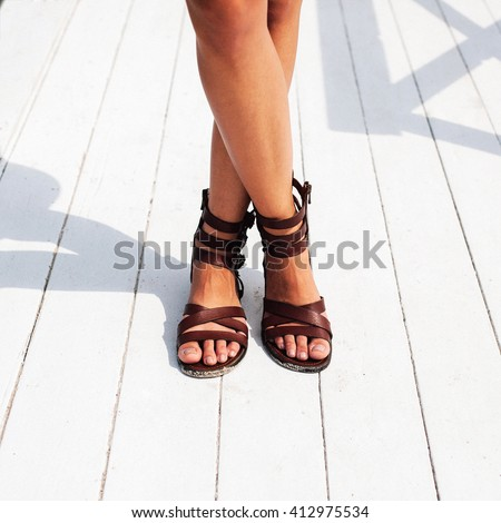 Closeup of tanned legs on the street in summer in leather open shoes  - stock photo