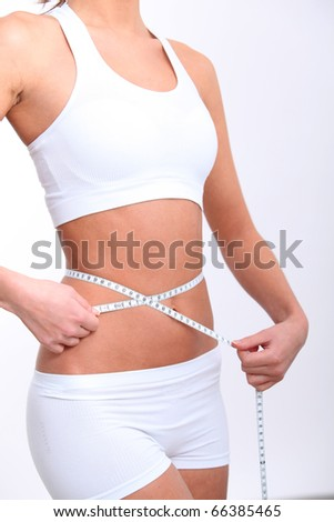 Closeup of tape measure around woman waist - stock photo