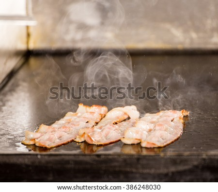 Closeup of Tasty Fried Bacon Strips on Grilling Panel. Delicious Cooked Bacon Rashers Close-Up, Bacon Roasting Grill or Barbecue Plate with Plenty of Steam. - stock photo